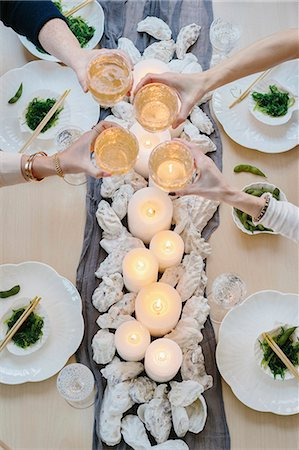 Overhead view of four people sharing a meal, plates of sushi and a table setting for a celebration meal. Stock Photo - Premium Royalty-Free, Code: 6118-08659836