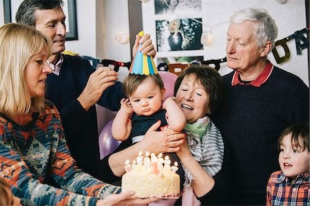 shy baby - A family gathered to celebrate a one year old girl's birthday party. A cake with lots of candles. Stock Photo - Premium Royalty-Free, Code: 6118-08659997