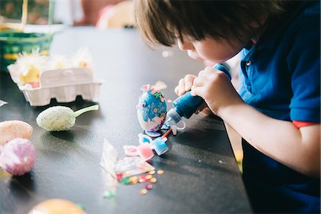 A child decorating eggs at Easter with glitter, glue and paint. Stock Photo - Premium Royalty-Free, Code: 6118-08660001