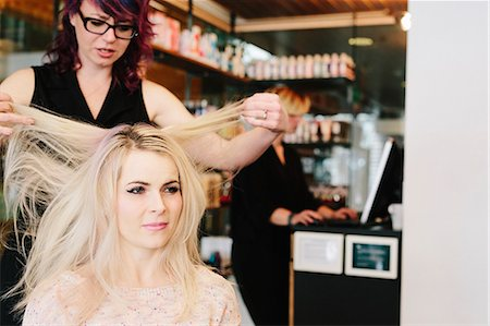 A hair stylist and a client, a young woman with long blonde hair, at a hair salon. Stock Photo - Premium Royalty-Free, Code: 6118-08660009