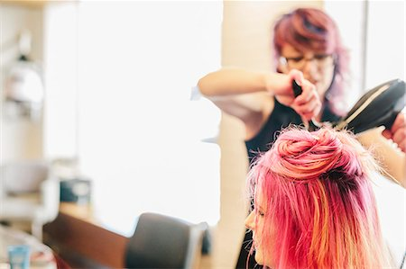 A hair stylist blow-drying a client's long pink dyed hair. Stock Photo - Premium Royalty-Free, Code: 6118-08660203