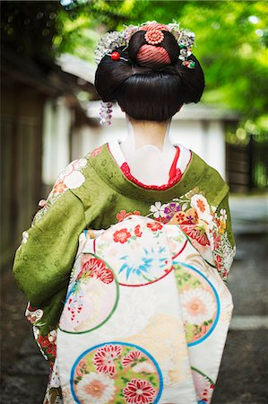 A woman dressed in the traditional geisha style, wearing a kimono and obi, with an elaborate hairstyle and floral hair clips, with white face makeup with bright red lips and dark eyes on a street. Stock Photo - Premium Royalty-Free, Code: 6118-08761755