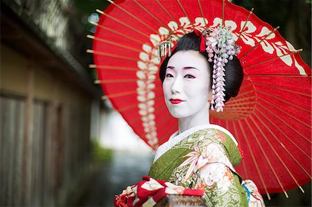 A woman dressed in the traditional geisha style, wearing a kimono and obi, with an elaborate hairstyle and floral hair clips, with white face makeup with bright red lips and dark eyes holding a red paper parasol. Stock Photo - Premium Royalty-Free, Code: 6118-08761758