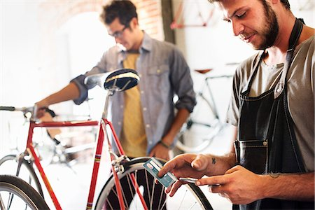 southern california - Two men in a cycle repair shop, one holding a smart phone and credit card. Paying by contactless card. Stock Photo - Premium Royalty-Free, Code: 6118-08725671