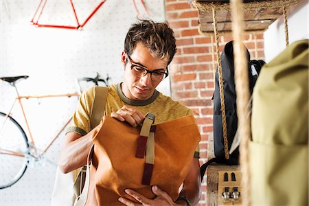 southern california - A customer in a bike shop, looking at a backpack. Stock Photo - Premium Royalty-Free, Code: 6118-08725675