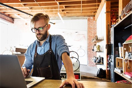 southern california - A man in a bicycle repair shop using a laptop computer.  Running a business. Stock Photo - Premium Royalty-Free, Code: 6118-08725679