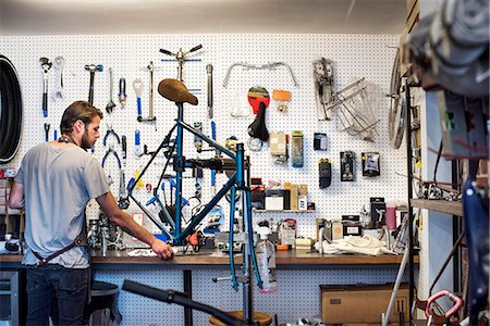 southern california - A man working in a bicycle repair shop. Stock Photo - Premium Royalty-Free, Code: 6118-08725684