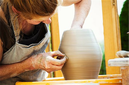 A woman potter working clay on a potter's wheel in her workshop. Stock Photo - Premium Royalty-Free, Code: 6118-08725953