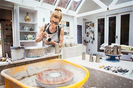 A potter handling a wet clay pot, preparing it for kiln firing. Stock Photo - Premium Royalty-Free, Code: 6118-08725963