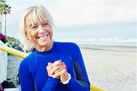 southern california - Smiling senior woman wearing a wetsuit, standing on a sandy beach. Stock Photo - Premium Royalty-Free, Code: 6118-08726065