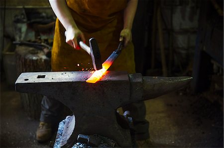 A blacksmith strikes a length of red hot metal on an anvil with a hammer in a workshop. Stock Photo - Premium Royalty-Free, Code: 6118-08729044