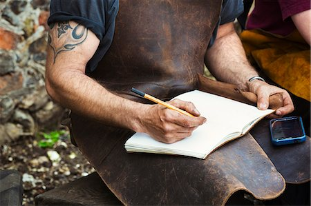 drawing (artwork) - Two people, man and woman blacksmiths wearing leather aprons writing into a notebook sat in a garden. Stock Photo - Premium Royalty-Free, Code: 6118-08729049