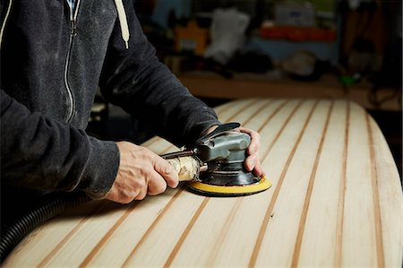 A man finishing the surface of a wooden surfboard with an electrical sander. Stock Photo - Premium Royalty-Free, Code: 6118-08860580