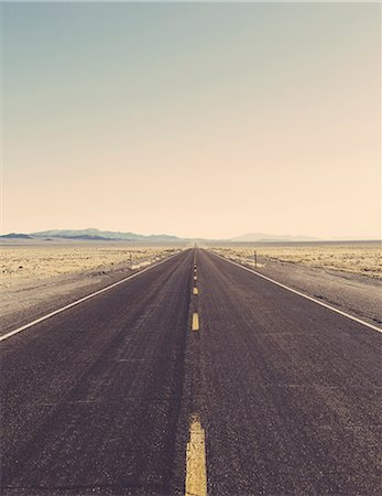 Remote rural road through a flat arid landscape to the horizon. Stock Photo - Premium Royalty-Free, Code: 6118-08860599