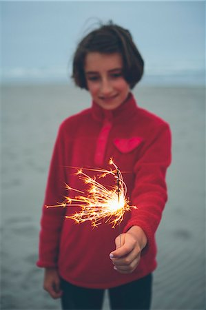 A young girl holding a lighted sparkler on the beach at dusk. Stock Photo - Premium Royalty-Free, Code: 6118-08827554