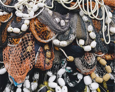 Close up of a pile of tangled up commercial fishing nets with floats attached. Stock Photo - Premium Royalty-Free, Code: 6118-08910527