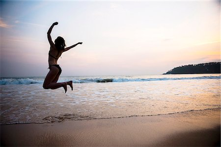 exotic outdoors - Tourist jumping on Mirissa Beach at sunset, South Coast of Sri Lanka, Southern Province, Sri Lanka, Asia Stock Photo - Premium Royalty-Free, Code: 6119-07451163