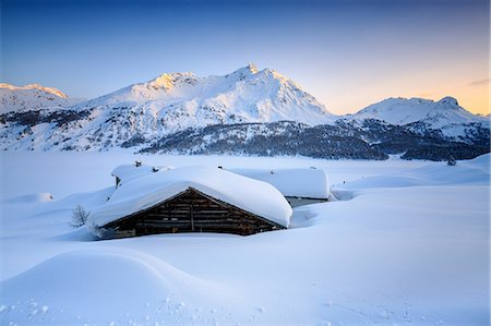 extreme terrain - Some scattered huts in a snowy landscape at Spluga by the Maloja Pass with the magical colors of the sunset, Graubunden, Swiss Alps, Switzerland, Europe Stock Photo - Premium Royalty-Free, Code: 6119-08062106