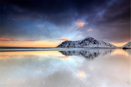 dreamy - Sunset on Skagsanden beach surrounded by snow covered mountains reflected in the cold sea, Flakstad, Lofoten Islands, Arctic, Norway, Scandinavia, Europe Stock Photo - Premium Royalty-Free, Code: 6119-08170184