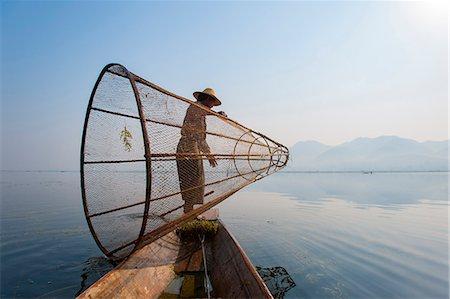 A basket fisherman on Inle Lake prepares to plunge his cone shaped net, Shan State, Myanmar (Burma), Asia Stock Photo - Premium Royalty-Free, Code: 6119-08703691