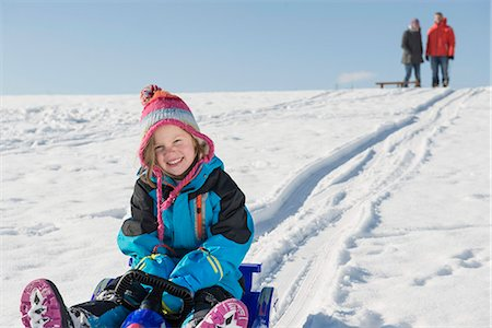 Portrait of girl sledging down hill while her parents watching, Bavaria, Germany Stock Photo - Premium Royalty-Free, Code: 6121-07740054
