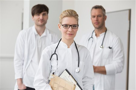dependable - Female doctor with file while colleagues in background Stock Photo - Premium Royalty-Free, Code: 6121-07740088