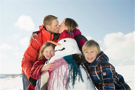 Girl and boy standing with snowman, parents kissing in background, Bavaria, Germany Stock Photo - Premium Royalty-Free, Code: 6121-07740003