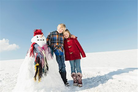 Girl and boy with snowman, smiling, Bavaria, Germany Stock Photo - Premium Royalty-Free, Code: 6121-07740006