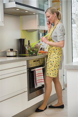 Woman talking on phone while preparing salad in kitchen Stock Photo - Premium Royalty-Free, Code: 6121-07740153