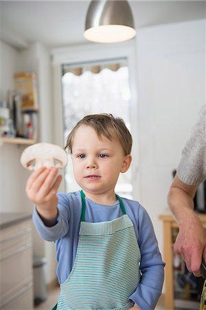 Boy holding mushroom slice in kitchen Stock Photo - Premium Royalty-Free, Code: 6121-07740157