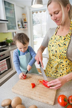 Mother cutting vegetables with her son, smiling Stock Photo - Premium Royalty-Free, Code: 6121-07740155