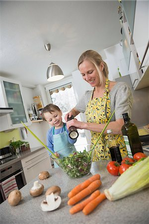Boy preparing salad with his mother, smiling Stock Photo - Premium Royalty-Free, Code: 6121-07740162