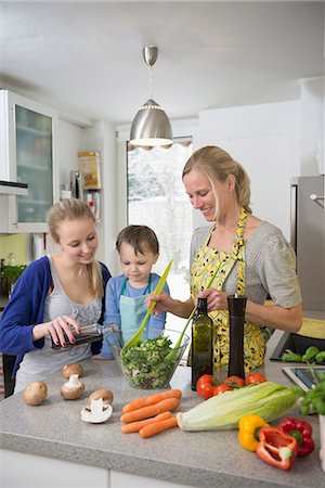 Mother and children preparing salad in kitchen, smiling Stock Photo - Premium Royalty-Free, Code: 6121-07740170