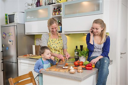 Mother and son grating vegetables while daughter talking on phone Stock Photo - Premium Royalty-Free, Code: 6121-07740177
