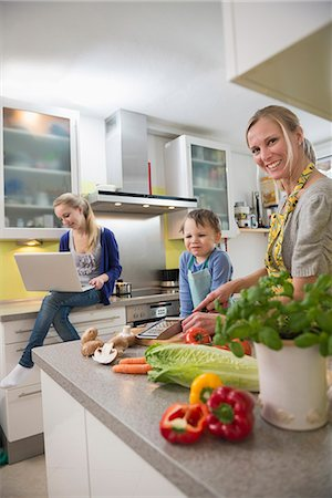 Mother and son preparing food while daughter using laptop in background Stock Photo - Premium Royalty-Free, Code: 6121-07740175