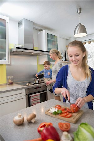 Daughter cutting vegetables while mother with son in background Stock Photo - Premium Royalty-Free, Code: 6121-07740185