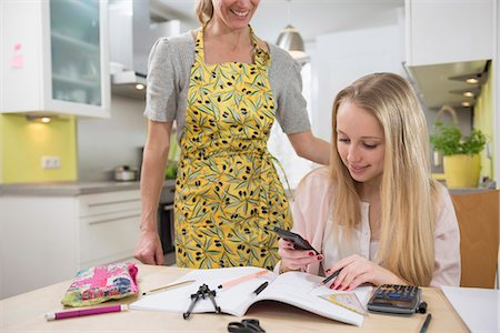 Mother helping daughter with homework, smiling Stock Photo - Premium Royalty-Free, Code: 6121-07740242
