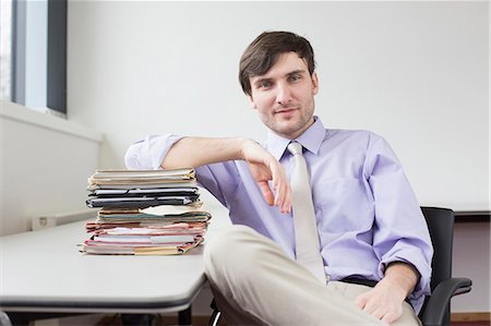 piles of work - Portrait of businessman sitting in office with stack of files Stock Photo - Premium Royalty-Free, Code: 6121-07740253