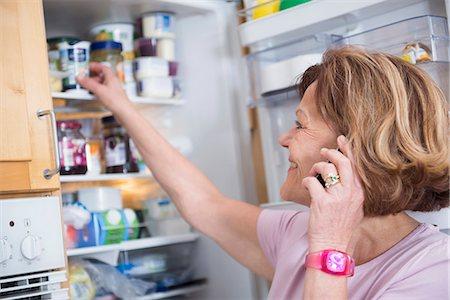 fridge - Senior woman infront of open refrigerator, smiling Stock Photo - Premium Royalty-Free, Code: 6121-07740263