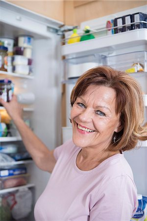 fridge - Portrait of senior woman infront of open refrigerator, smiling Stock Photo - Premium Royalty-Free, Code: 6121-07740262