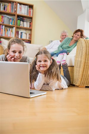 pantyhose kid - Granddaughters using laptop while grandparents in background Stock Photo - Premium Royalty-Free, Code: 6121-07740287