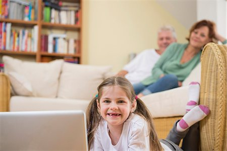 pantyhose kid - Granddaughter using laptop in living room while grandparents in background Stock Photo - Premium Royalty-Free, Code: 6121-07740284