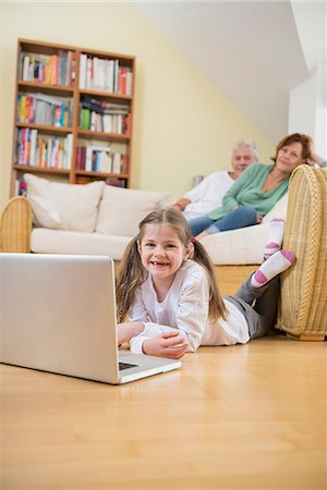 pantyhose kid - Granddaughter using laptop in living room while grandparents in background Stock Photo - Premium Royalty-Free, Code: 6121-07740285