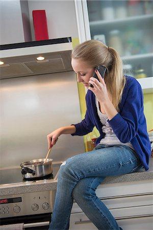 sitting - Teenage girl talking on phone while stirring in pot Stock Photo - Premium Royalty-Free, Code: 6121-07740214