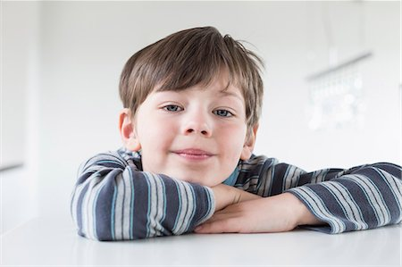 Portrait of boy leaning on table, close up Stock Photo - Premium Royalty-Free, Code: 6121-07740357