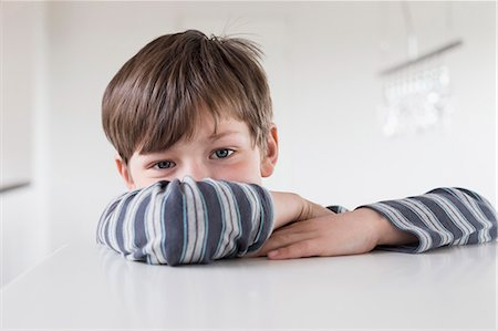Portrait of boy leaning on table, close up Stock Photo - Premium Royalty-Free, Code: 6121-07740358