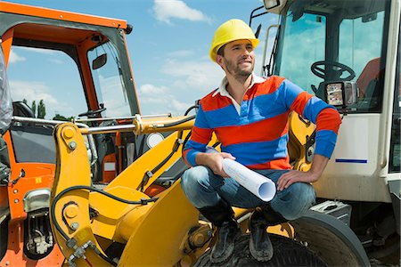 picture - Construction worker sitting on excavator holding construction plan Stock Photo - Premium Royalty-Free, Code: 6121-07740300