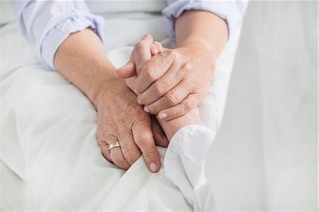 Woman holding patient's hand Stock Photo - Premium Royalty-Free, Code: 6121-07740453
