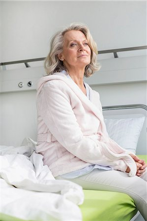 Patient in hospital sitting on bed Stock Photo - Premium Royalty-Free, Code: 6121-07740457