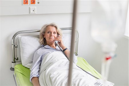 Patient in hospital phoning from bed Stock Photo - Premium Royalty-Free, Code: 6121-07740463